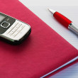 Phone and pencil with a notebook. A close up — Foto de Stock