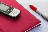 Phone and pencil with a notebook. A close up — Foto Stock