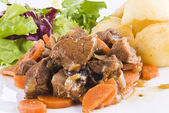 Stewed beef steak with potatoes and salad — Stock Photo