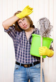 Tired man with cleaning supplies — Stock Photo
