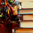 Books laying in front of Chrismas tree — Stock Photo #4577133