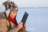 Teen girl reading e-book outdoors at winter time — Stock Photo