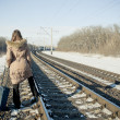 Teen girl with suitcase near railways at winter time — Stock Photo #4818171
