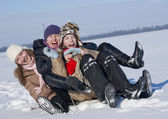 Happy sisters sledding at winter time — Stock Photo