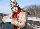 Teen girl with a suitcase near the railways at winter time — Foto de Stock