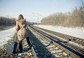 Dospívající dívka s kufrem blízko železnice v zimním období — Stock fotografie