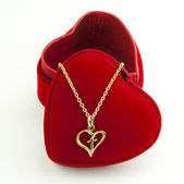 Necklace and heart shaped red box — Stock Photo