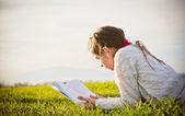 Muchacha leyendo un libro sobre la hierba — Foto de Stock