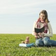 Girl reading a ebook sitting at grass — Stock Photo