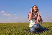 Girl with headphones listening music outdoors — Stock Photo