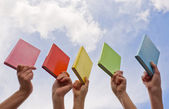 Hands holding color hard cover books — Stock Photo