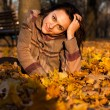 Stock Photo: Beautiful young woman lying in autumn leaves