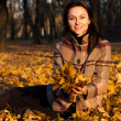 Beautiful young woman sitting in autumn leaves — Stock Photo