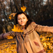 Royalty-Free Stock Photo: Beautiful young woman throwing autumn leaves