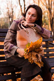 Beautiful young woman on a bench in autumn — Foto de Stock