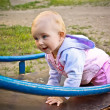 Beautiful baby girl climbing a slide in playground — Stock Photo