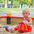 Little baby girl sitting playing in a sandbox in playground outdoor — Stock Photo
