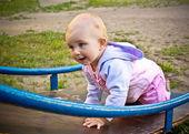 Beautiful baby girl climbing a slide in playground — Stock Photo