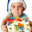 Girl in Santa's hat giving out s present — Stock Photo
