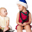 Baby looking at the sibiling sister in Santa's hat — Stock Photo