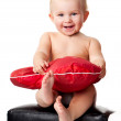 Royalty-Free Stock Photo: Beautiful baby sitting with heart shaped red pillow
