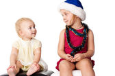 Baby looking at the sibiling sister in Santa's hat — 图库照片