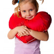 Beautiful girl with heart shaped pillow — Stock Photo