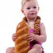 Baby holding a loaf of bread in roll beads — Stock Photo #4450664