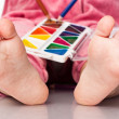 Baby's feet with paint and pencils — Stock Photo