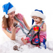 Stock Photo: Mother and daughter in Santa's hat sitting in artificial snow