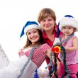Family in Santa's hat lying in artificial snow — Stock Photo