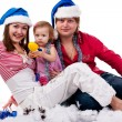 Stock Photo: Family in Santa's hat lying in artificial snow