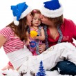 Royalty-Free Stock Photo: Parents in Santa\'s hat kissing their child in artificial snow