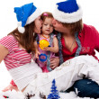 Parents in Santa's hat kissing their child in artificial snow - Stock Photo