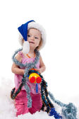 Baby in Santa's hat in tinsel and artificial snow — Stock Photo