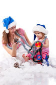 Mother and daughter in Santa's hat sitting in artificial snow — Stock Photo