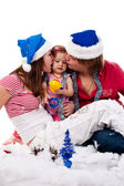 Parents in Santa's hat kissing their child in artificial snow — Stock Photo