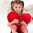 Beautiful girl sitting with heart shaped red pillow — Stock Photo