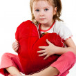 Royalty-Free Stock Photo: Beautiful girl sitting with heart shaped red pillow