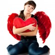 Beautiful girl sitting with heart shaped red pillow in red angel wings — Stock Photo