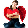 Royalty-Free Stock Photo: Beautiful girl sitting with heart shaped red pillow in red angel wings
