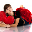 Beautiful girl lying with heart shaped red pillow in red angel wings — Stock Photo #4583167