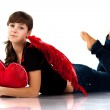 Beautiful girl lying with heart shaped red pillow in red angel wings — Stock Photo