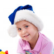 Royalty-Free Stock Photo: Beautiful girl in Santa\'s hat in tinsel and artificial snow
