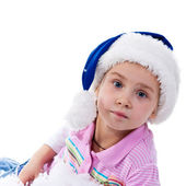 Beautiful girl in Santa's hat in tinsel and artificial snow — Stock Photo