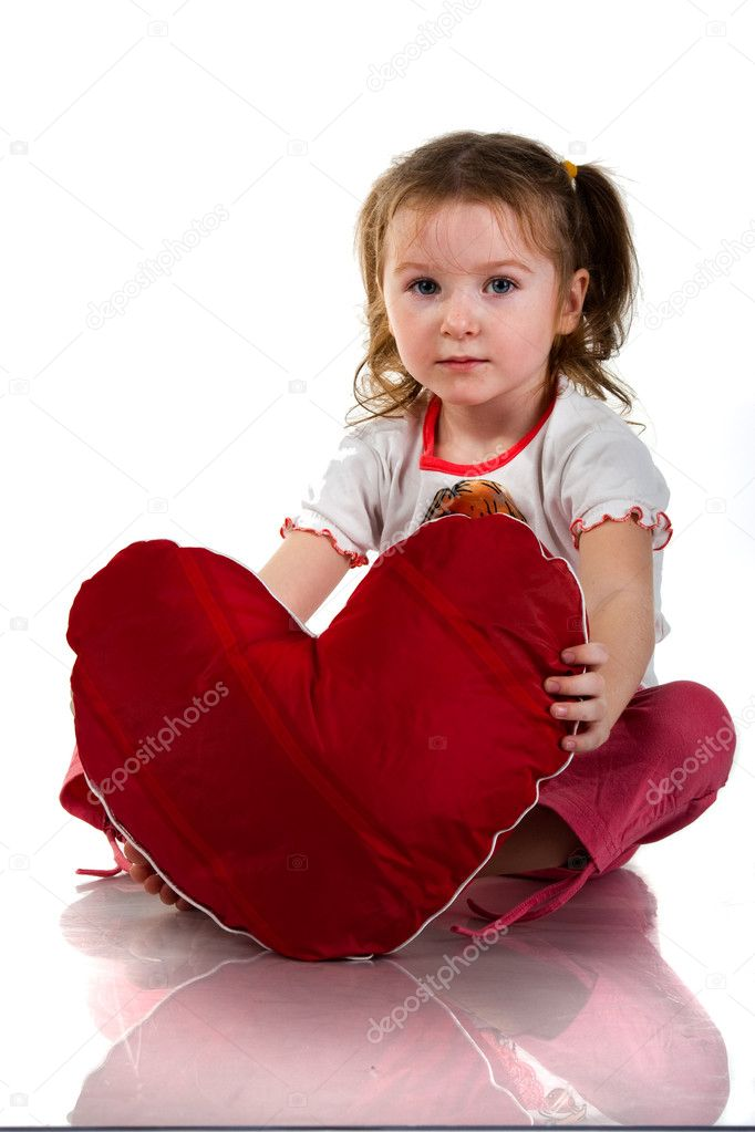 Beautiful girl sitting with heart shaped red pillow isolated on white — Stock Photo #4583163