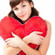 Beautiful girl with heart shaped red pillow — Stock Photo