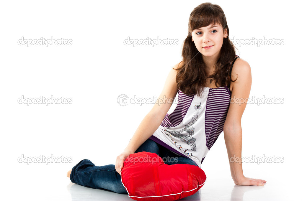 Beautiful girl sitting with heart shaped red pillow  isolated on white — Stock Photo #4635929