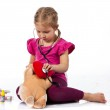Beautiful girl playing doctor with a doll — Stock Photo