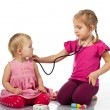 Children playing doctor with a doll — Stock Photo